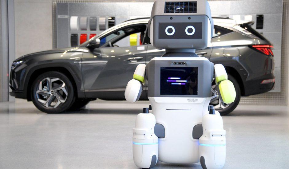 Le robot DAL-e se tient devant une voiture Hyundai.