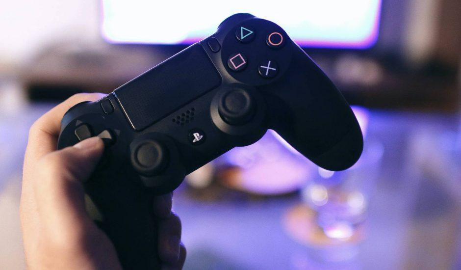 Une personne tient une manette de PlayStation dans la main.