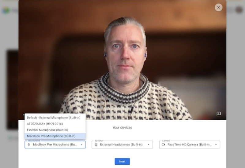 Un homme ajuste les paramètres avant un appel sur Google Meet.