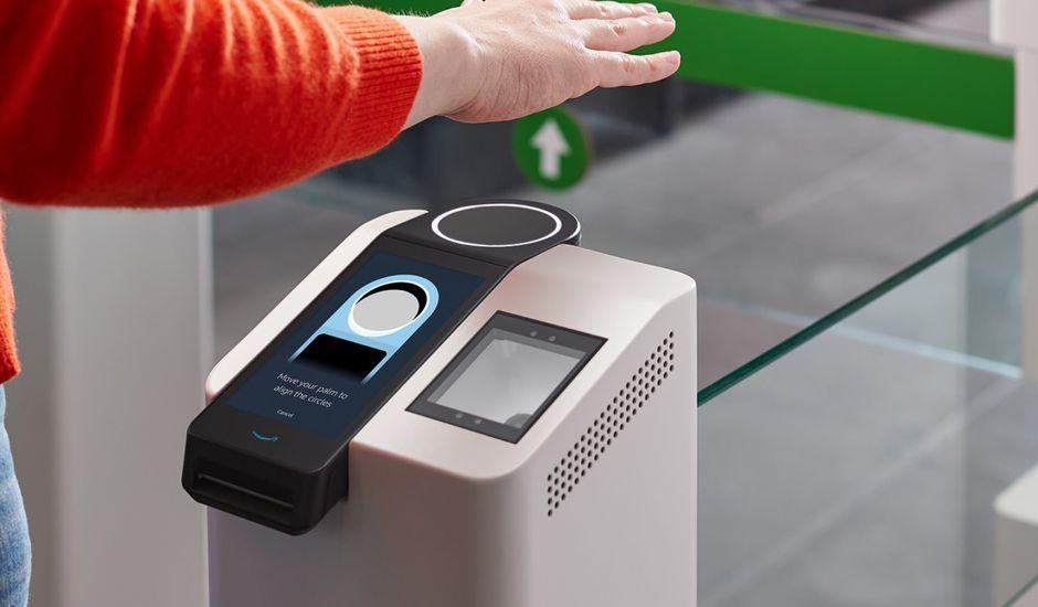 Une personne présente sa main au-dessus d'un scanner pour effectuer un paiement.
