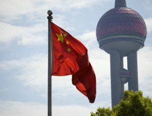 Le drapeau chinois devant un édifice à Shanghai.