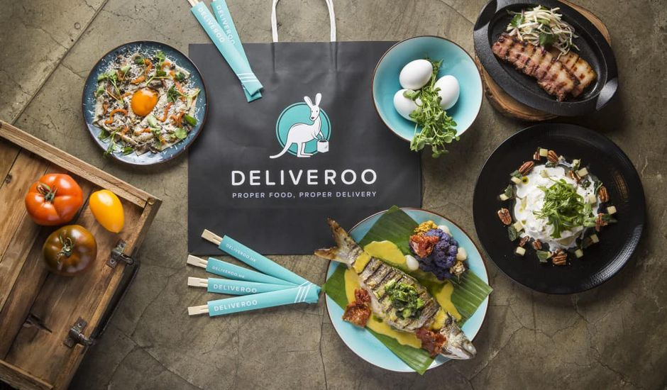 Un sac de courses Deliveroo posé sur une table de cuisine avec différents plats