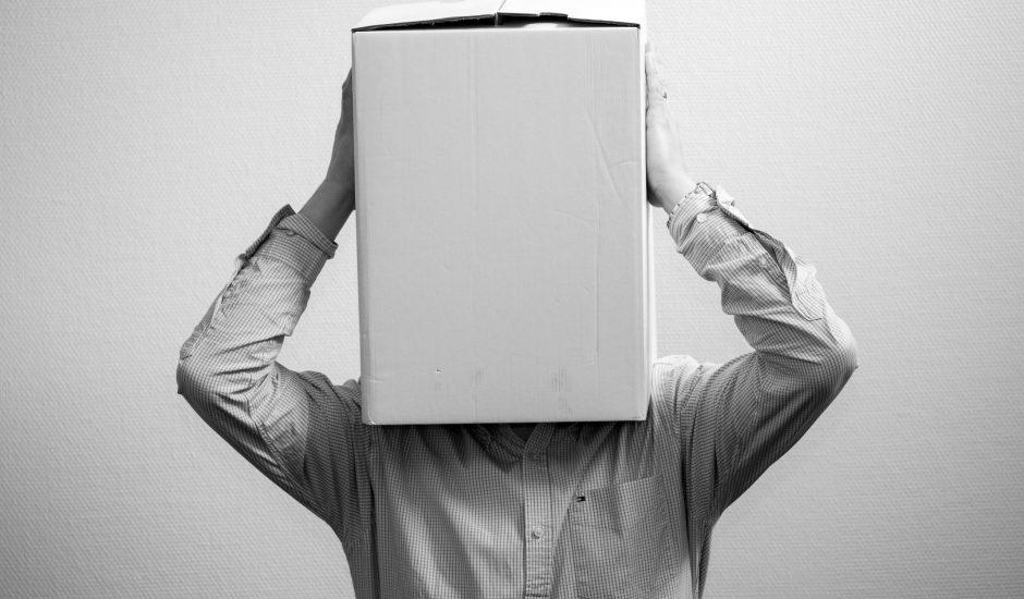 Une personne portant une chemise avec la tête dans un carton