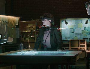 Trois personnes utilisant Microsoft Mesh se tiennent debout face à une table numérique lors d'une réunion.