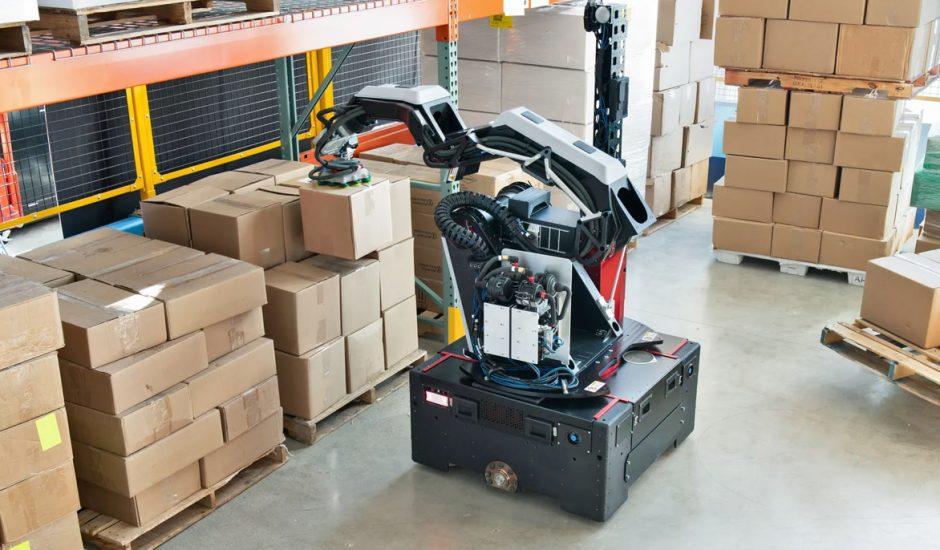 Le robot Stretch de Boston Dynamics soulève des cartons dans un entrepôt.