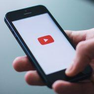 Un homme tient un smartphone qui lance l'application YouTube.