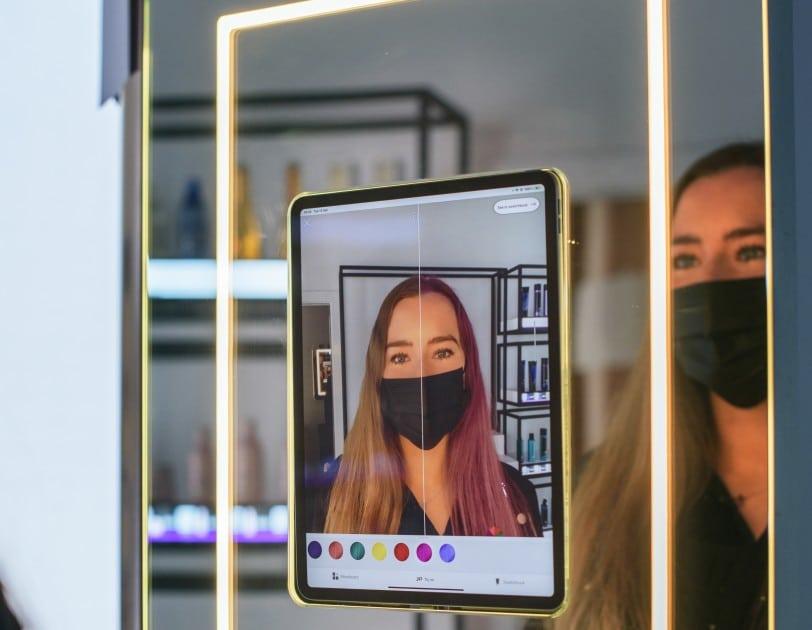 une femme essayant une nouvelle couleur de cheveux grâce à la réalité augmentée d'Amazon Salon