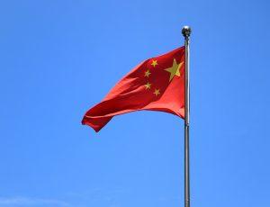Le drapeau chinois flotte devant un ciel bleu.