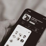 Une personne tenant un smartphone dans la main, avec la page de Clubhouse sur l'App Store d'Apple.