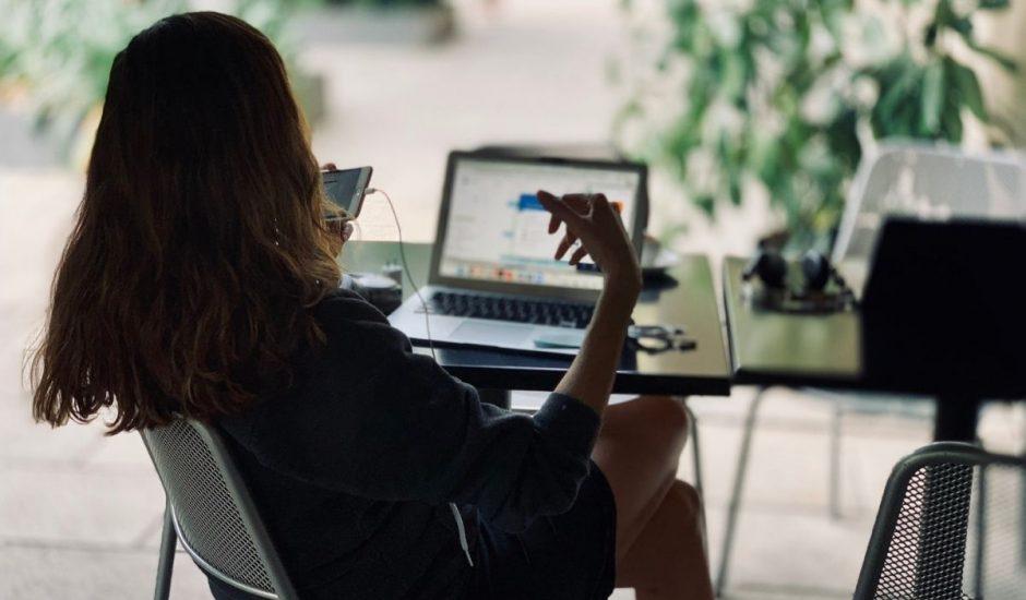 une professionnelle du digital devant son ordinateur et son smartphone