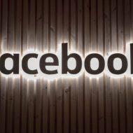 Le logo Facebook illuminé sur un mur en bois.