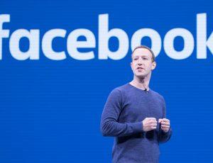 Mark Zuckerberg debout devant le logo de Facebook.