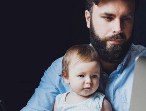 Un homme en télétravail avec un enfant sur ses genoux