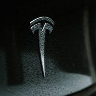 Le logo Tesla sur le pare-chocs d'une voiture.
