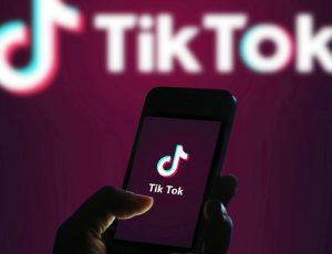 Photographie du logo TikTok avec une personne qui tient son portable dans les mains. La méthode de travail 996 est controversée.