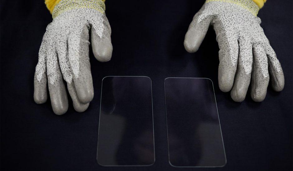 Des mains portant des gants travaillent sur le verre d'écrans.