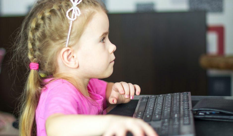 Une petite fille devant un ordinateur