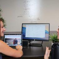 deux employées échangeant devant leur ordinateur