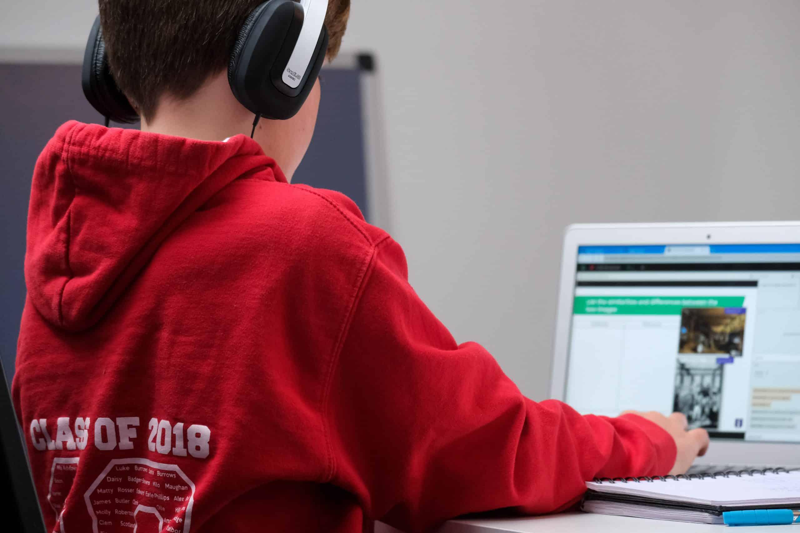 Un jeune élève utilise un ordinateur en classe, afin de faire des recherches ou préparer des exposés.