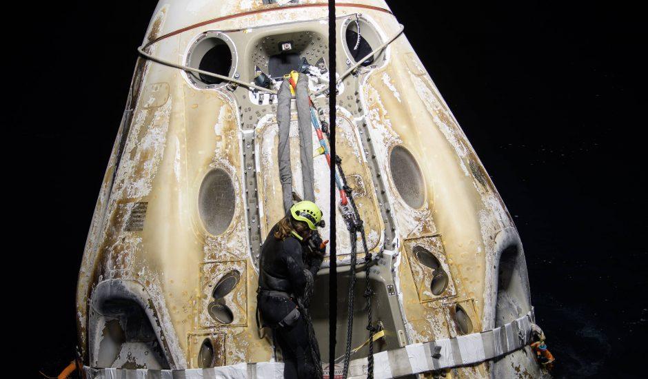 La capsule Crew Dragon flottant sur l'eau quelques minutes après son arrivée sur Terre, alors que le personnel de SpaceX travaille à son ouverture.