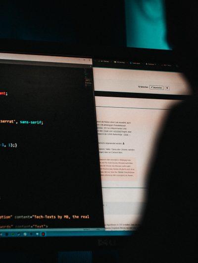 Un homme de dos en train de coder sur un ordinateur.