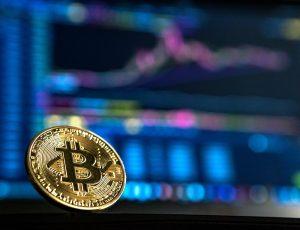 Une pièce de bitcoin devant un écran d'ordinateur.