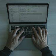 Un homme tape sur un clavier d'ordinateur portable/