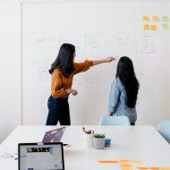 deux employées discutant face à un tableau blanc