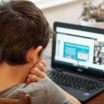 Un jeune garçon devant un ordinateur.