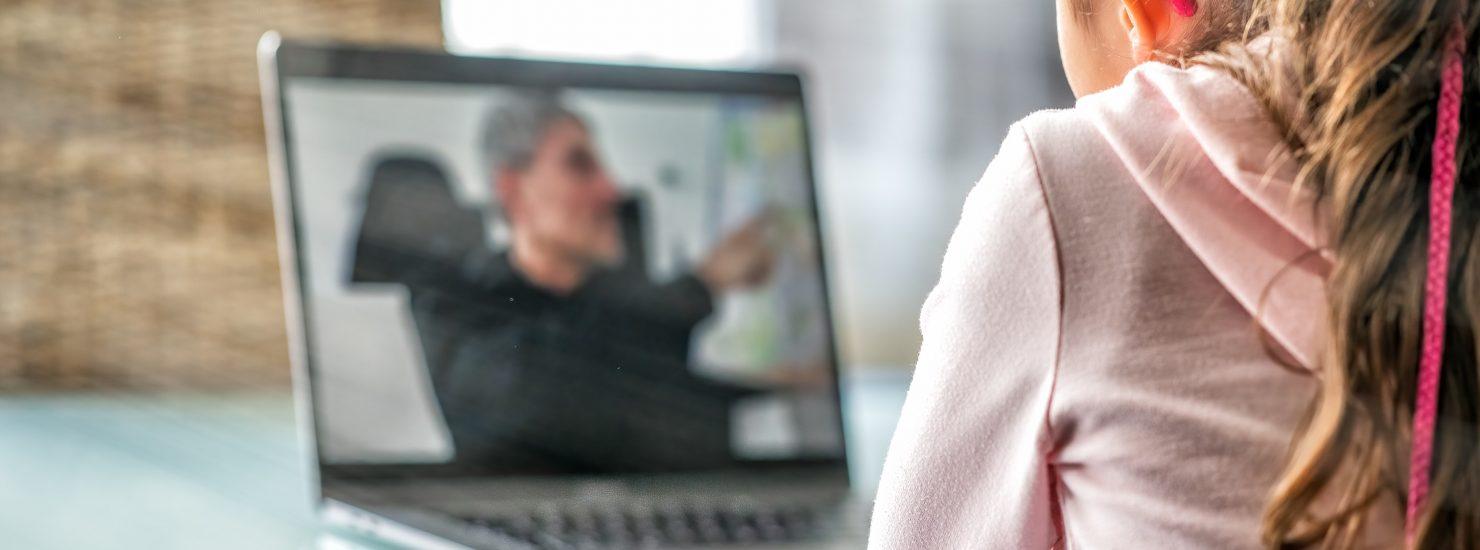 Une jeune élève suit un cours à distance sur son ordinateur portable.