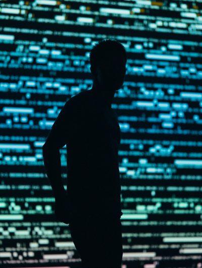 Photographie d'un homme dont on voit que la forme devant un tableau numérique. La Quadrature du net met en cause la CNIL dans le non respect du RGPD par les GAFAM