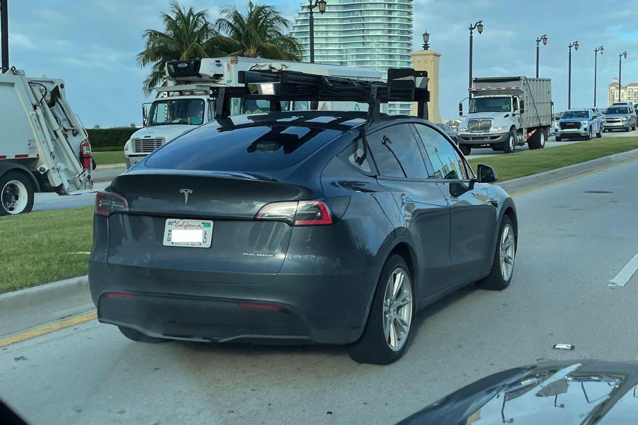 une voiture tesla grise avec des capteurs LIDAR sur son toit