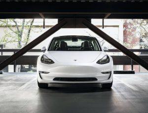 Un véhicule Tesla blanc garé dans un parking.