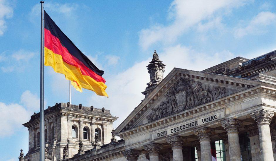 Le drapeau allemand flotte devant un monument.