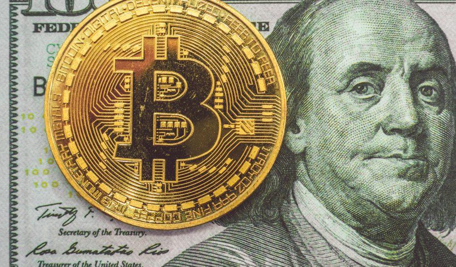 Photographie d'un bitcoin sur un de 100 dollars américains. Le dollar est la monnaie officielle du Salvador.