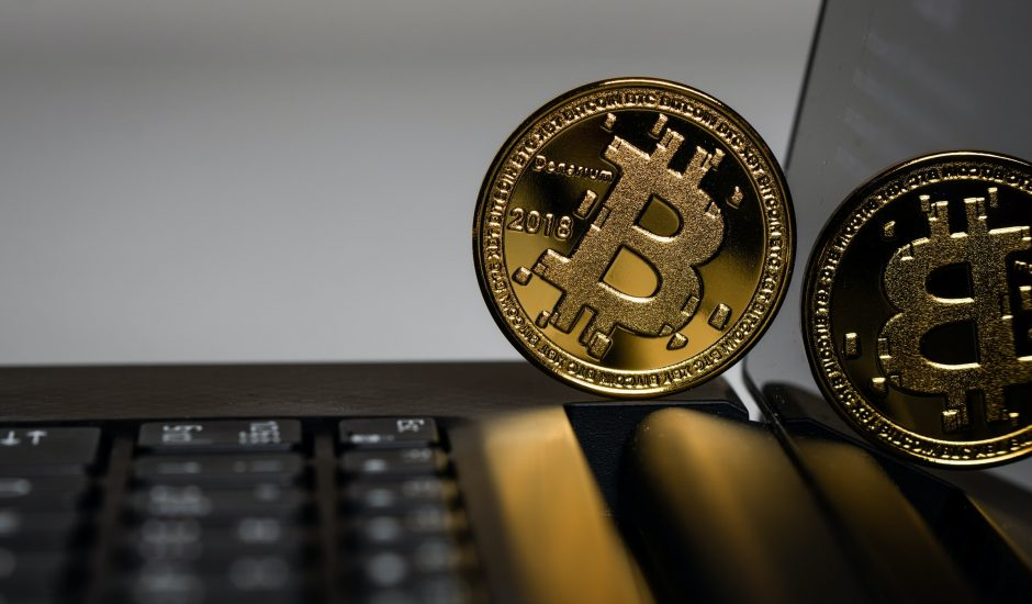 Photographie d'un bitcoin tenant en équilibre sur un ordinateur portable.
