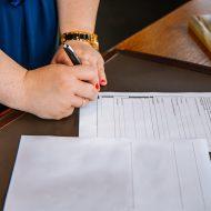 Photographie d'une femme signant un contrat. L'Europe a publié des clauses contractuelles sur les transferts de données hors de l'union européenne.