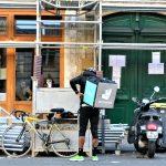 Photographie d'un livreur Deliveroo devant un restaurant.