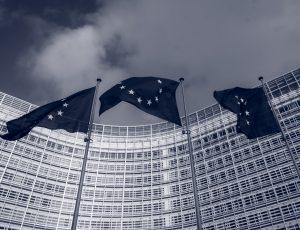 Trois drapeaux européens devant un bâtiment officiel.