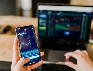 Photographie d'une personne tenant un smartphone avec l'écran affichant le cours de crypto-monnaies. Au second plan se trouve un ordinateur.