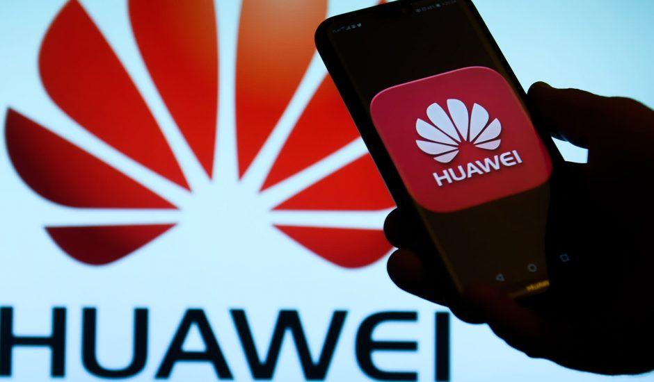 Photographie d'une main tenant un smartphone avec le logo Huawei à l'écran et en fond derrière.