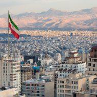 Photographie d'une ville en Iran avec le drapeau de l'Iran.