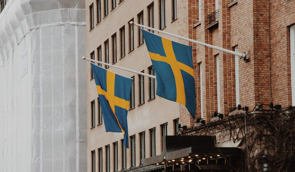 Photographie de deux drapeaux suédois sur un bâtiment.