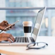 une femme sur son ordinateur et son téléphone