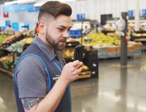 Un employé de Walmart tenant un smartphone dans sa main.