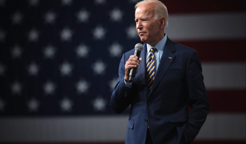 Joe Biden tenant un micro devant un drapeau américain
