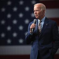 Joe Biden avec un micro devant le drapeau américain