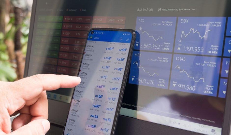 Photographie d'un ordinateur et d'un smartphone présentant des indices boursiers.