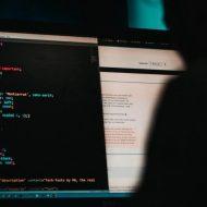 Une personne en train de coder derrière un PC.