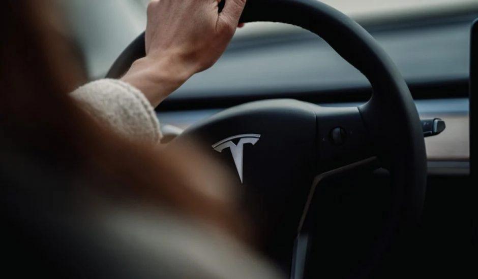 Une conductrice derrière le volant d'une Tesla.